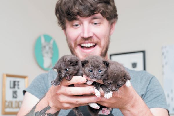 Adam Myatt holding a litter of kittens.