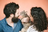 A cat kissing his two humans.