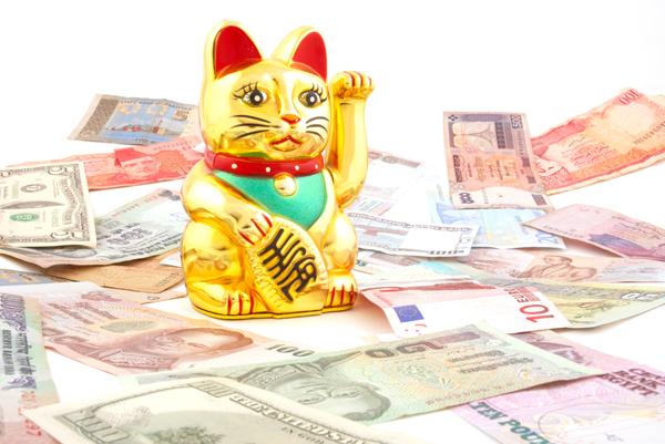 Un Maneki Neko, o gato de la suerte, rodeado de dinero.