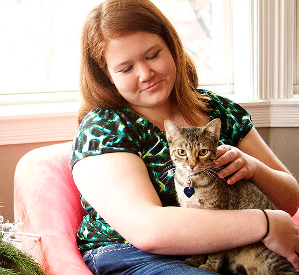 A student holds a foster cat at a holiday gathering at Stephens College.