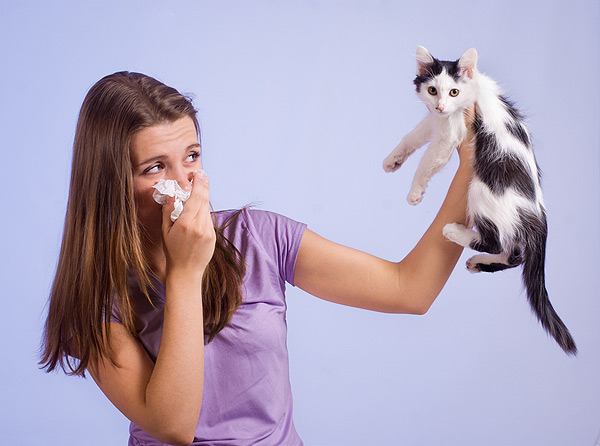 A woman sneezing and holding up a cat.
