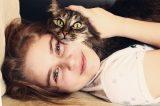 A teenage girl hugs a cat.
