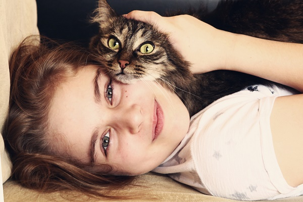 A teenage girl hugs a cat.