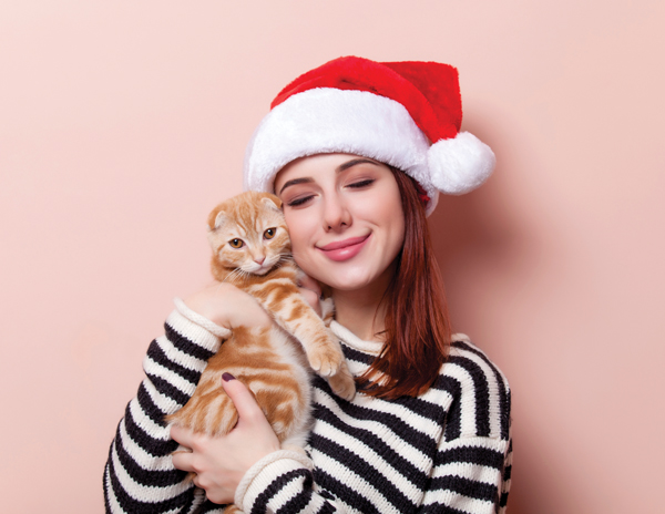 Portrait of a young redhead woman in Santa Claus hat with ginger scottish fold cat on pink background