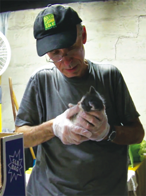 Stu takes care of a kitten rescued from the streets. Photo courtesy of The Cat Rescuers, used by permission.