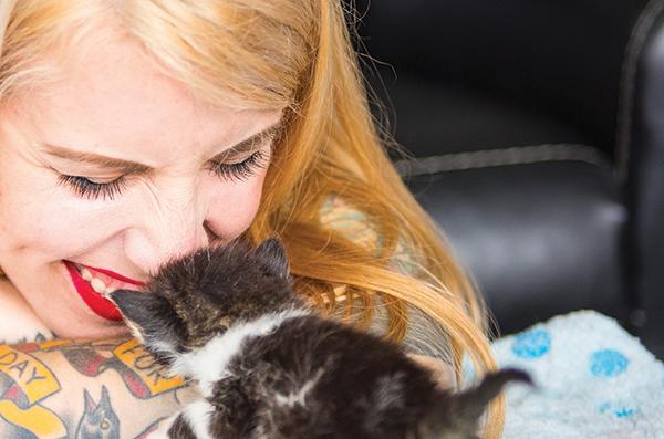 A blonde cat lady kissing a kitten.