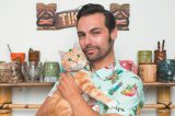 A cat guy or cat daddy holding an orange tabby cat.