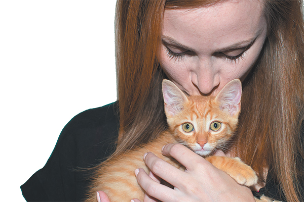 A woman kissing an orange cat.
