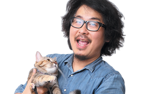 A man with glasses holding a cat that's looking up.