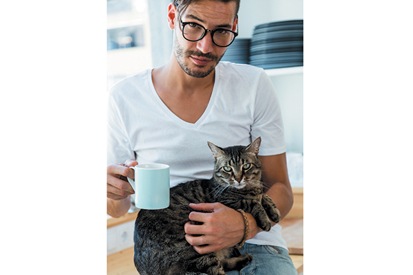 A hot cat guy sipping coffee.