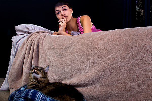 A woman shushing a cat meowing at night.