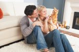 A man and a woman cuddling a ginger tabby cat.
