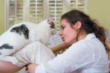 A woman talking to or kissing a cat.
