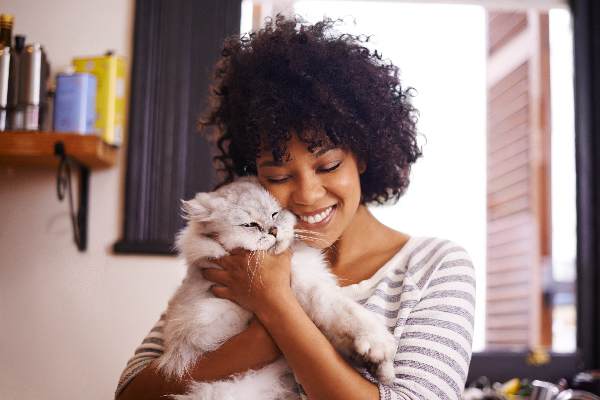 A woman hugging a cat.
